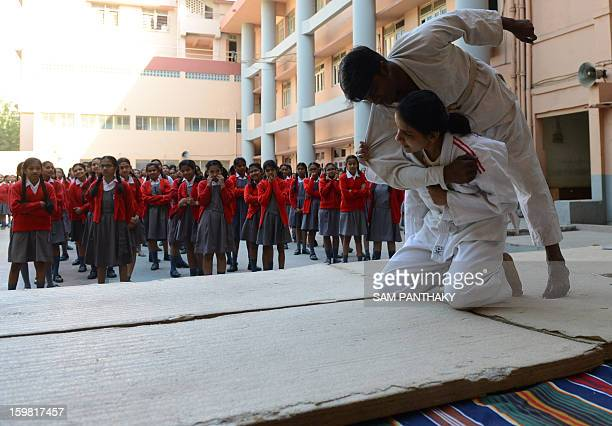 Indian female high school students watch an exhibition of basic Judo skills as they participate in a camp for self defense in Ahmedabad on January 21...