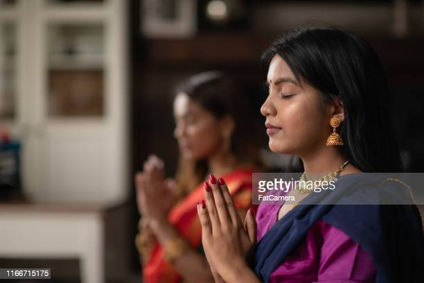indian females praying one afternoon in their living room - religious celebration stock pictures, royalty-free photos & images