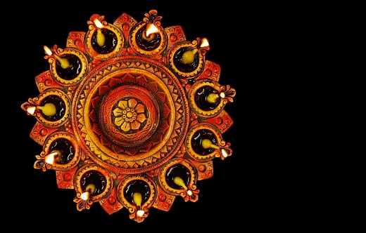 Indian Festival Diwali Deepawali being celebrated by lighting Diya Lamps Lights Prayer and Celebrations over black background 1175018890
