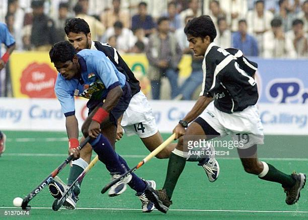 Indian field hockey player Ignace Tirkey gets past Pakistan hockey players Shakeel Abbasi and Adnan Zakir during the third field hockey match between...
