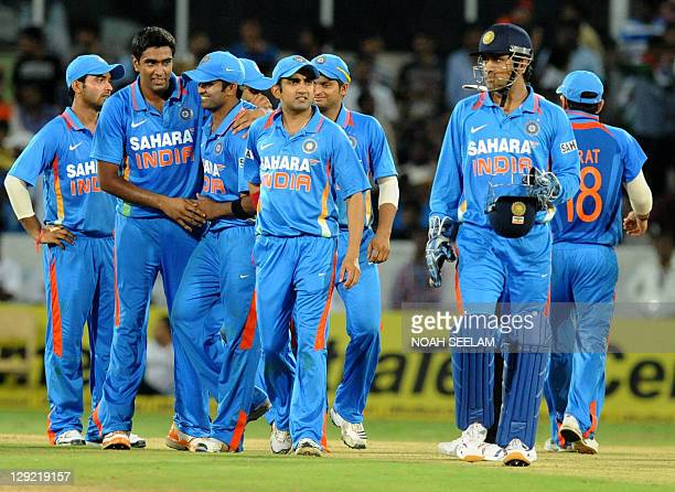 Indian fielder Ravichandran Ashwin celebrates with teammates after taking the wicket of unseen England batsman Ravi Bopara during the first one day...