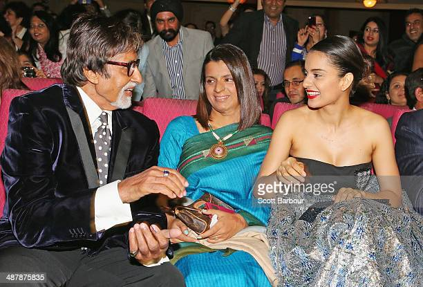 Indian film actor, Amitabh Bachchan greets Indian actress, Kangana Ranaut as her sister Rangoli Ranaut looks on during the Indian Film Festival of...