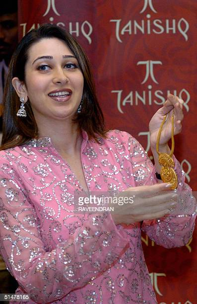 Indian film actress Karisma Kapoor unveils a bracelet during a product launch by jewellery firm Tanishq in New Delhi 14 October 2004 Tanishq has...
