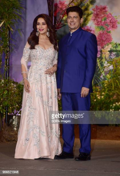 Indian film actress Madhuri Dixit with husband Sriram Nene attend the wedding reception of actress Sonam Kapoor and Anand Ahuja at hotel Leela in...