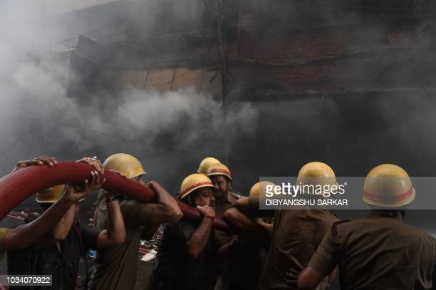 Indian fire fighters spray water to extinguish a fire at Bagree market building in Kolkata on September 16 2018