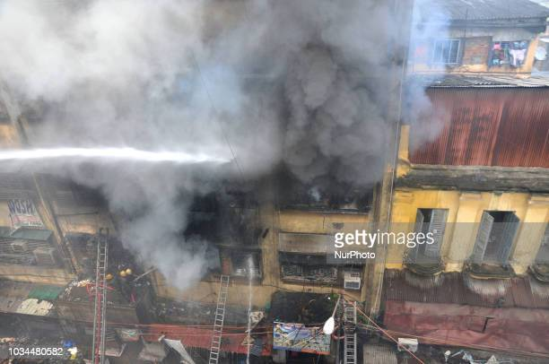Indian fire fighters spray water to extinguish a fire at Bagree market building in Kolkata on September 16 2018 A massive fire broke out in a...