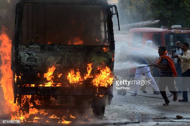 Indian fire fighters sprays water on a bus to control fire , in Allahabad on April 2017. Allahabad University witnessed large scale violence and...