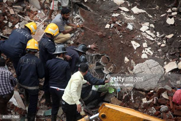 Indian fire officials look for survivors in the debris at site of a collapsed building in Mumbai on July 25, 2017. At least six people were crushed...