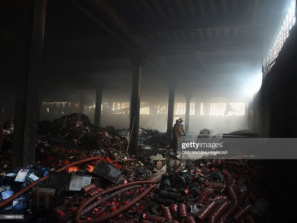 Indian firefighters control a blaze at a godown in Kolkata on January 3, 2013. A fire destroyed a century old warehouse at Burrabazar, the commercial hub of the eastern region, destroying goods comprising cloth and other inflammable material, a report said. AFP PHOTO/Dibyangshu SARKAR