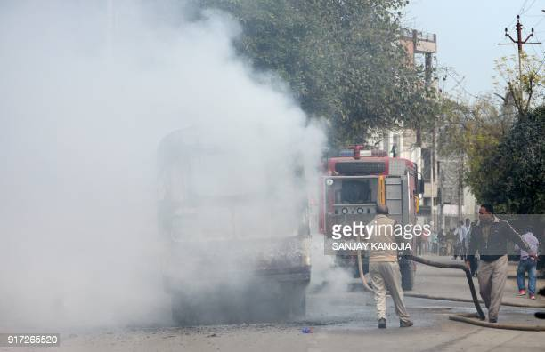 Indian firefighters extinguish a fire on a bus set by protesters near Allahabad University in Allahabad on February 12 2018 over the murder of a...