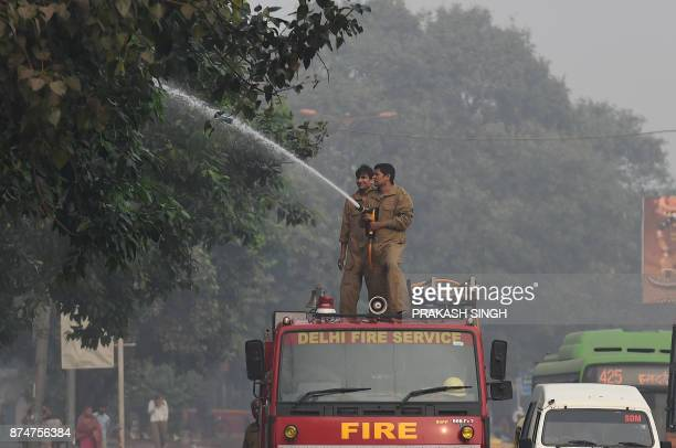 Indian firefighters spray water onto trees at the roadside in a bid to curb air pollution by combatting accumulated dust in New Delhi on November 16...