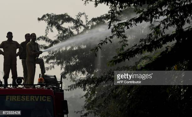 Indian firefighters spray water onto trees on the roadside in a bid to curb air pollution by combatting accumulated dust in New Delhi on November 10...