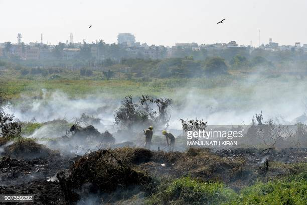 TOPSHOT Indian firefighters try to douse a fire at Bellandur Lake in Bangalore on January 20 2018 Bellandur Lake which is among the highly polluted...