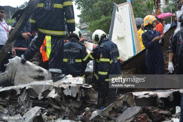 Indian firemen and aviation officials inspect the wreckage of a plane that crashed into a construction site killing five people in Mumbai on June 28...