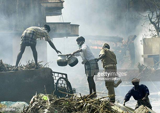 Indian firemen and volunteers collect water in an attempt to put out a fire which spread from a funeral pyre set to burn tidal wave victims in...