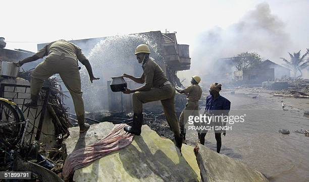 Indian firemen and volunteers throw water in an attempt to stop a fire which spread from a funeral pyre set to burn tidal wave victims in...