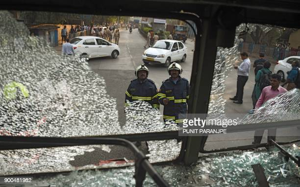 Indian firemen inspect a damaged bus after supporters of the Republican Party of India turned violent during a protest in Mumbai on January 2 2018...