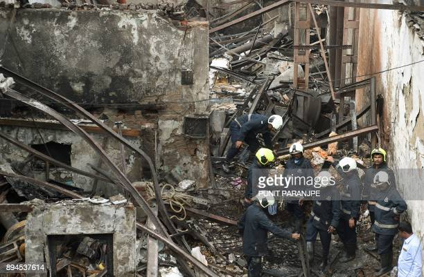 Indian firemen inspect the scene of a fire in Mumbai on December 18 2017 Fire tore through a sweet shop in the Indian city of Mumbai before dawn on...
