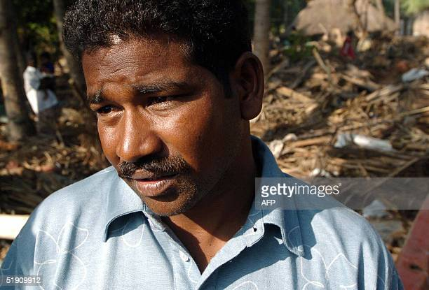 Indian fisherman Mohan Phupalam stands on damage created by tidal waves in Puthukuppam a fishing village some 20 kilometres from Pondicherry 03...