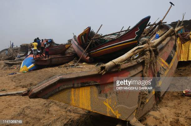 Indian fishermen assess damage to boats along the seafront in Puri in the eastern Indian state of Odisha on May 4 after Cyclone Fani swept through...
