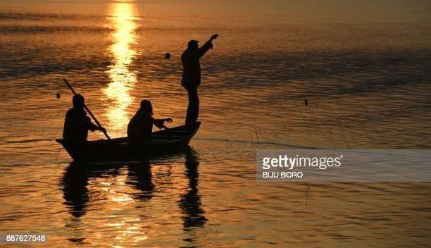 Indian fishermen fish at the Brahmaputra River during sunset in Guwahati on December 7 2017 / AFP PHOTO / Biju BORO