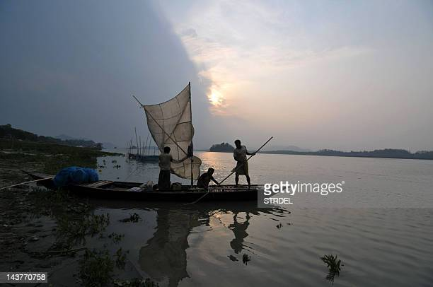 Indian fishermen guide their vessel to the banks of the River Brahmaputra in Guwahati on April 5 to offload their catch at The Uzanbazar Fish Market...