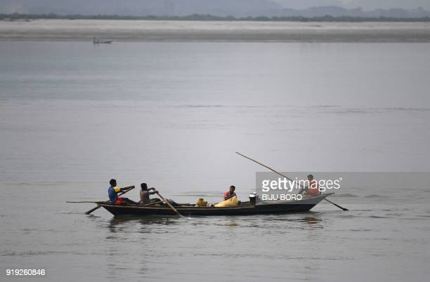 Indian fishermen paddy their boat at the Brahmaputra River as they go to sell their fishes in Guwahati on February 17 2018 The Brahmaputra originates...