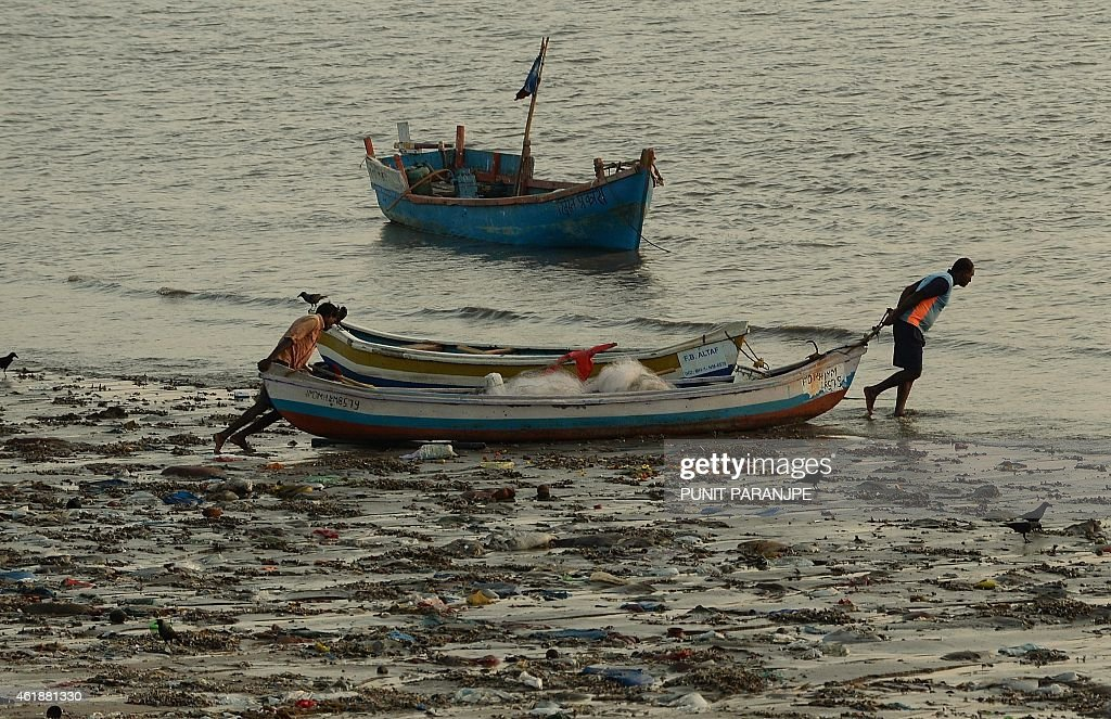 Indian fishermen push their boat through plastic waste into the sea in Mumbai on January 21, 2015. India is part of a global trend that is advancing towards an increasing urbanisation, with more than half of the world's population living in towns and cities.
