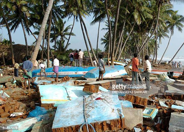 Indian fishermen search through the debris of huts and fishing boats in Cuddalore some 185 kms south west of Madras 28 December 2004 The Indian Red...