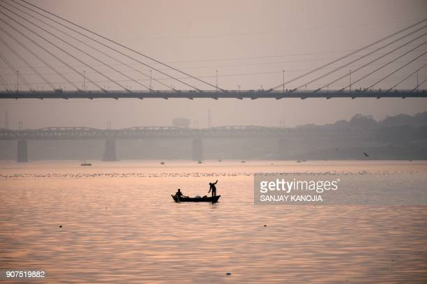TOPSHOT Indian fishermen work in the Yamuna river near Naini Yamuna Bridge in Allahabad on January 20 2018 / AFP PHOTO / SANJAY KANOJIA