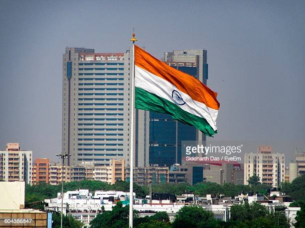 indian flag against buildings - indian flag stock pictures, royalty-free photos & images