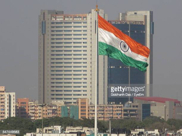 indian flag flying in front of skyscrapers - indian flag stock pictures, royalty-free photos & images