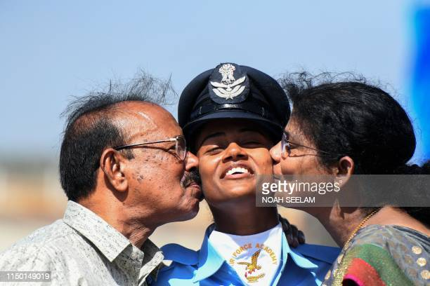 Indian Flight Cadet reacts as she is kissed by her parents after a combined graduation parade at the Indian Air Force Academy in Hyderabad on June 15...