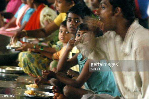 Indian flood victims eat a meal at a temporary NGO relief camp at Sangli 02 August 2006 Twelve people have lost their lives since 29 July due to...