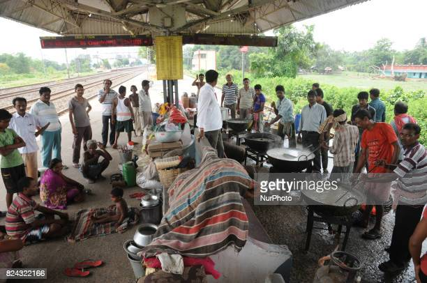 Indian flood victims eat cooked food distributed by volunteers a temporary shelter at a Railway Platform in Hooghly District Kolkata city to 70...