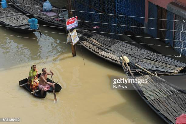 Indian flood victims on a boat make their way through flood waters after collecting relief materials in the Ghatal area of Paschim Medinipur distric...