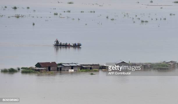 Indian flood victims travel by boat past the submerged village of Katoguri in Morigaon district in India's northeastern state of Assam on July 6 2017...