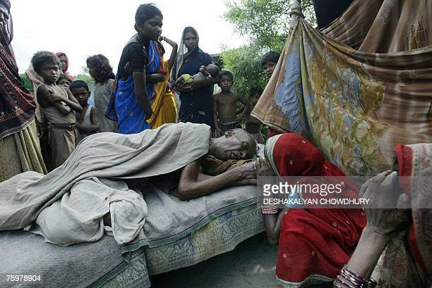 Indian floodaffected villagers mourn for Soukhi Paswan who died at a temporary shelter set up along the national highway beside their flooded...