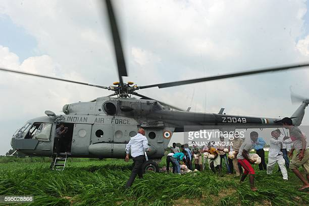 TOPSHOT Indian floodaffected villagers receive relief supplies distributed by defence personel from an Indian Air Force helicopter near Allahabad on...
