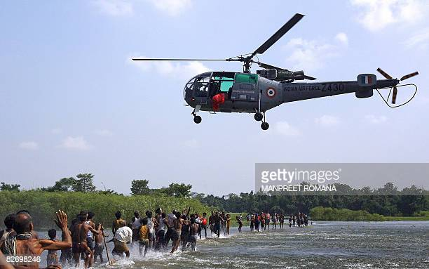 Indian floodaffected villagers run to collect relief material droped by a relief helicopter of the Indian Air Force in Madhepura district in India's...