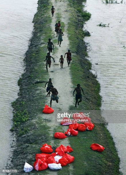 Indian floodaffected villagers run towards relief material dropped by the Indian Air Force near Birpur in Sapaul district in India's northeastern...