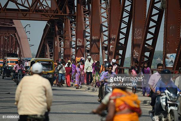 Indian followers of the late spiritual leader Jai Gurudev cross the Raj Ghat bridge to attend a Sabha a day after a fatal stampede in Varanasi on...