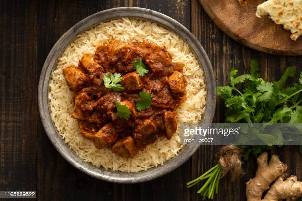 indian food chicken vindaloo curry over basmati rice - indian food stock pictures, royalty-free photos & images