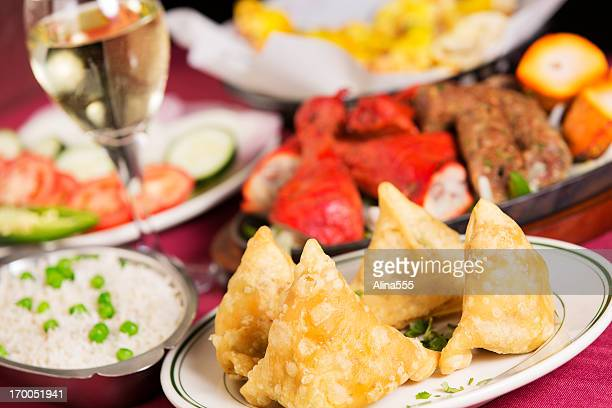 Indian food: samosas with rice, tandoori chicken, naan and vegetables