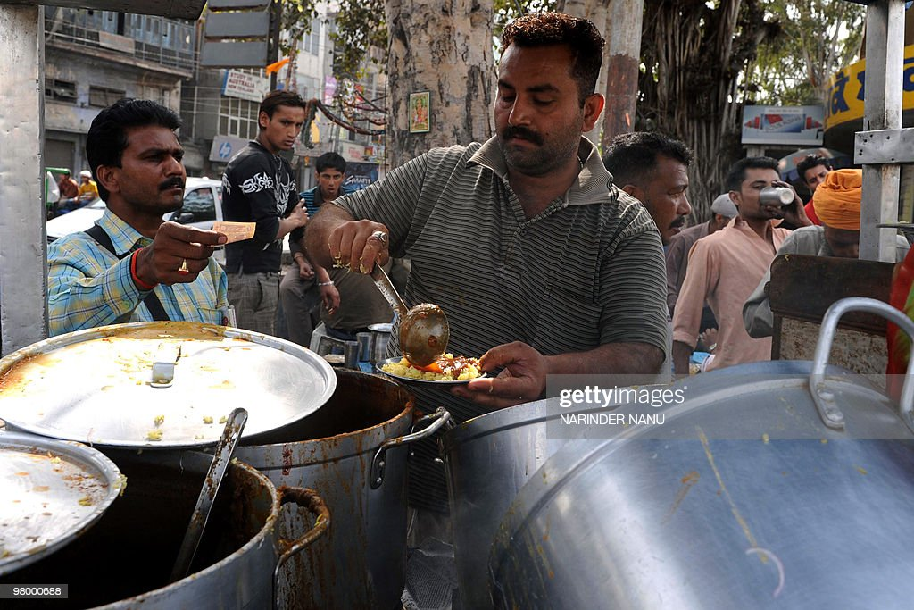 Indian food vendor Sonu Kumar ladles out food for a customer from his roadside stall in Amritsar on March 24 2010 Sonu sells a plate of rice with a...