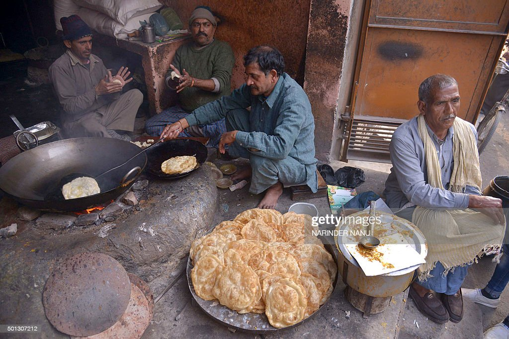 Indian food vendors prepare poori or puri fried puffed whole wheat flat bread and channa or chole masala chickpeas at a 56 yearold shop in Amritsar...