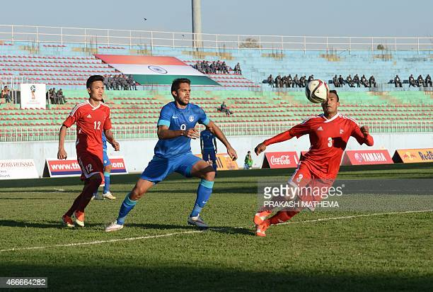 Indian football player Robin Singh and Nepal's Biraj Mahatjan vie for the ball during a 2018 FIFA World Cup qualifing match at Dasrath Stadium in...
