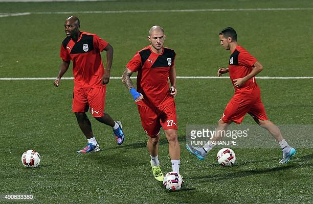 Indian football team Mumbai City FC players Frantz Bertin and Pavel Cmovs warm up with a teammate during a training session in Mumbai on October 1...