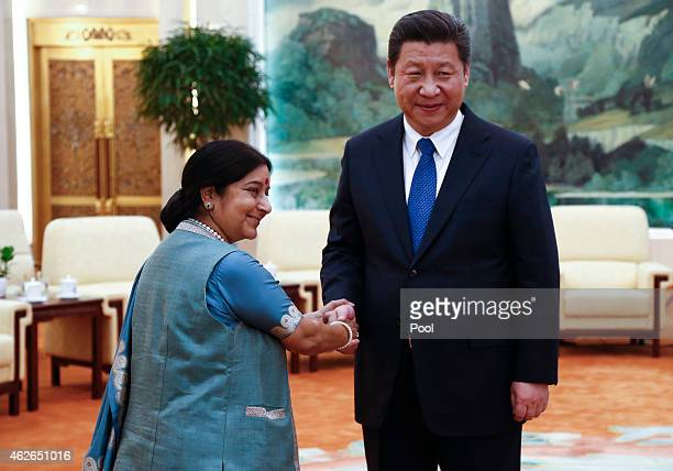 Indian Foreign Minister Sushma Swaraj and Chinese President Xi Jinping face the media as they greet each other before starting a meeting at the Great...