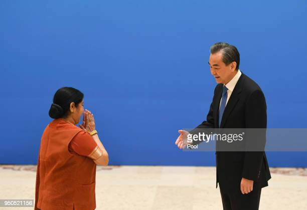 Indian Foreign Minister Sushma Swaraj moves to shake hands with Chinese State Councilor and Foreign Minister Wang Yi before a meeting of foreign...